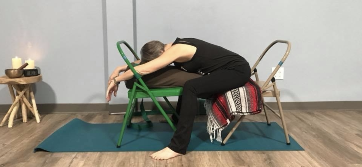 Moya McGinn Mathews demonstrates supported child's pose with two chairs and a bolster.