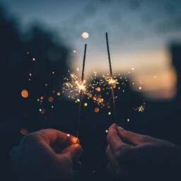 Two hands hold burning sparklers in the dark on New Year's Eve.