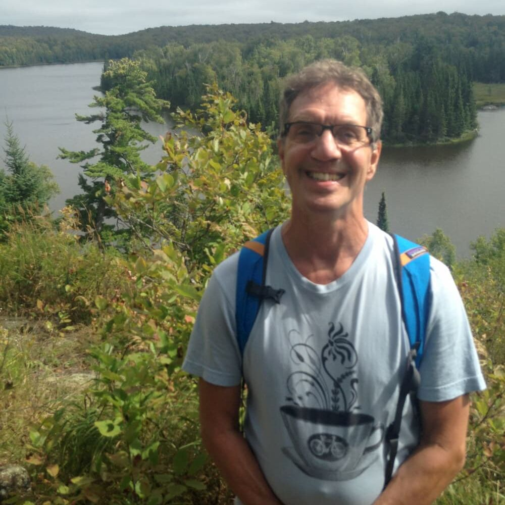William Prottengeier poses for a picture while hiking near a river wearing a backpack.