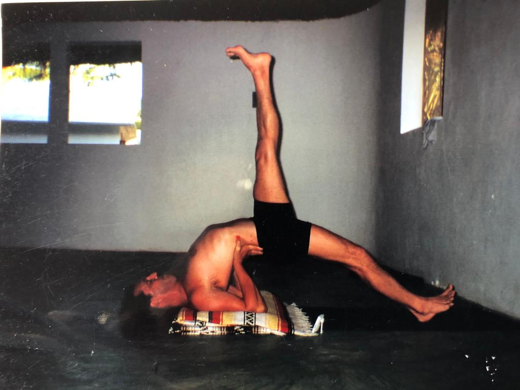 William demonstrates a shoulder stand variation with one leg extended to the floor and one in the air.